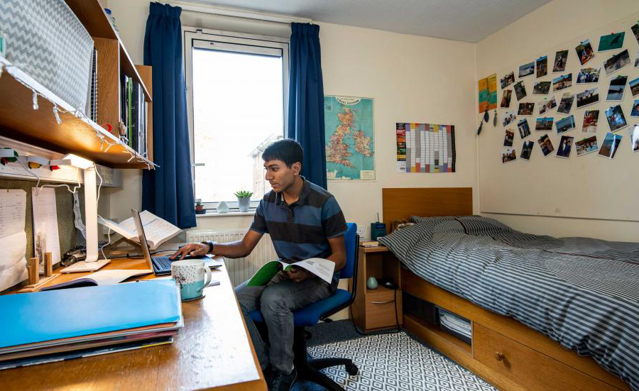 Student sat working at desk in bright, modern bedroom.